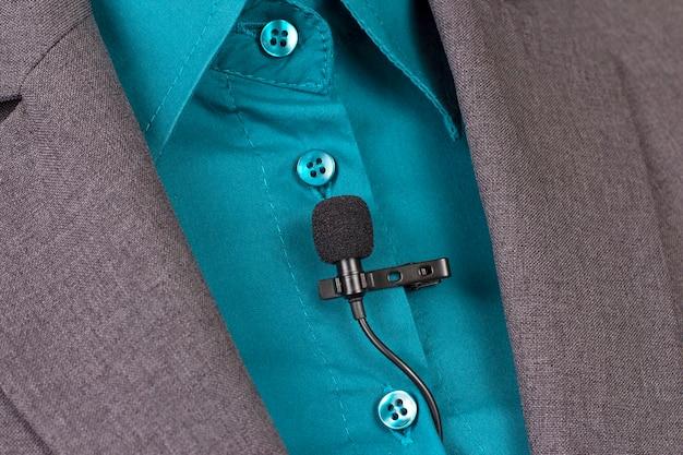 Le microphone cravate à clip est attaché au gros plan de vêtements pour femmes