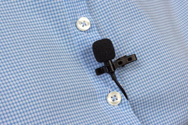 Le microphone cravate est fixé avec un clip sur un gros plan de chemise pour femme.