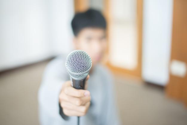 Microphone dans une main avec l'arrière-plan flou d'un garçon