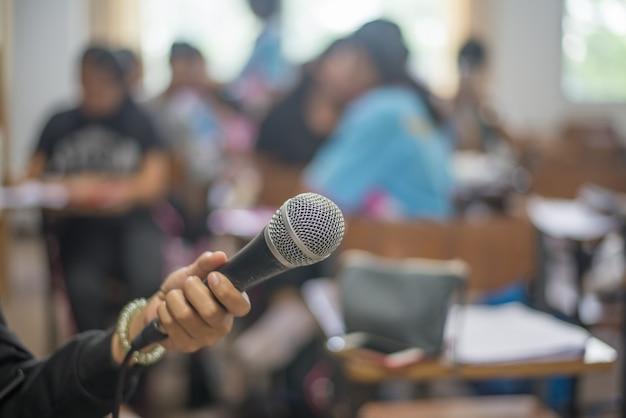 Microphone dans une main dans une salle de réunion