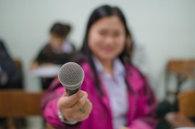 Microphone dans une main d'une femme dans une salle de classe