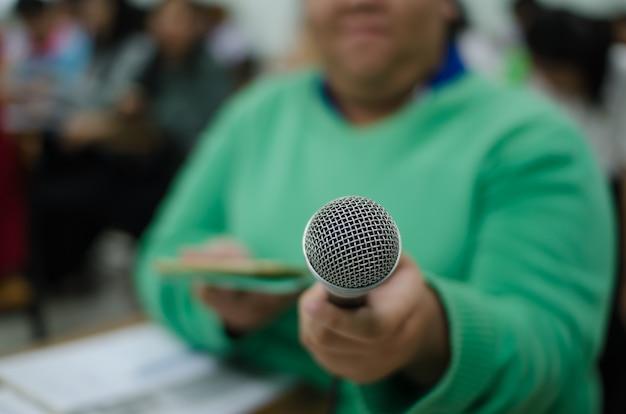 Microphone dans une main d'une femme en vert