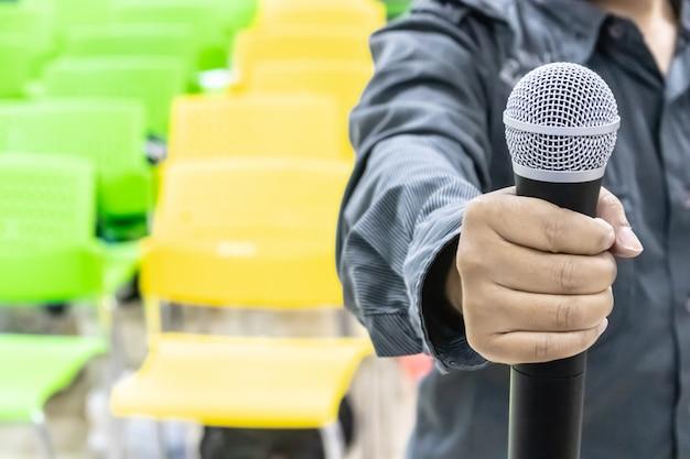 Microphone dans la main de l'homme avec des chaises de couleurs variées