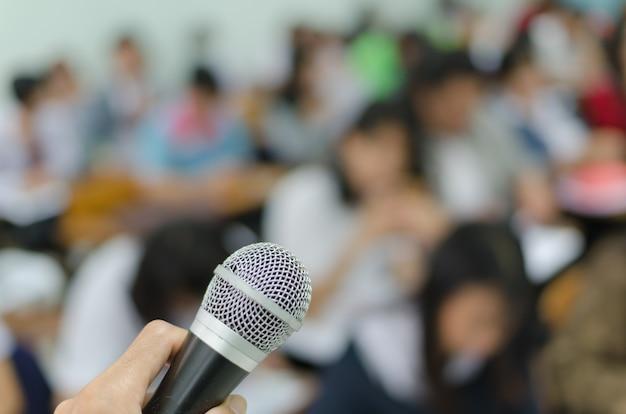 Microphone dans une main d'orateur devant la salle de conférence