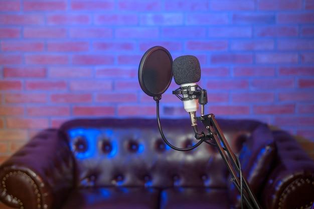 Un microphone dans un studio de musique avec des lumières colorées.