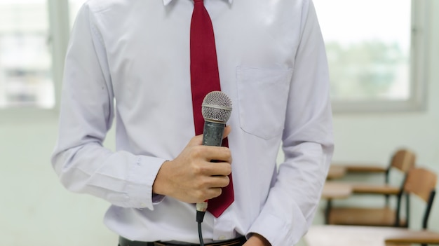 Le microphone est tenu par un homme avec une cravate rouge dans la salle de classe