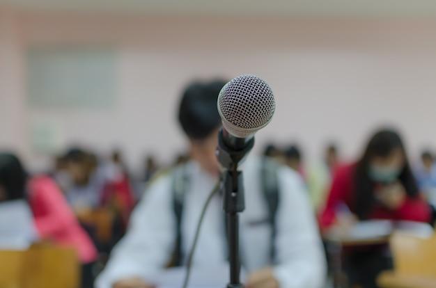 Microphone avec fond flou des étudiants travaillant dans la salle de classe