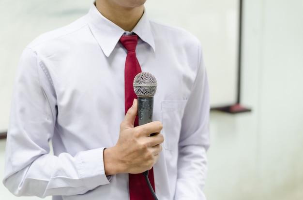 Microphone avec fond d'un homme en cravate debout devant le tableau blanc