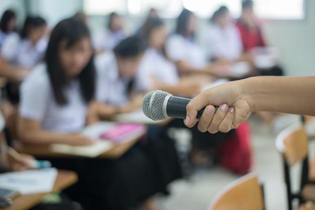 Microphone en main devant la salle de classe