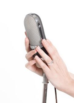 Microphone en métal entre les mains d'un chanteur de rock isolé sur fond blanc