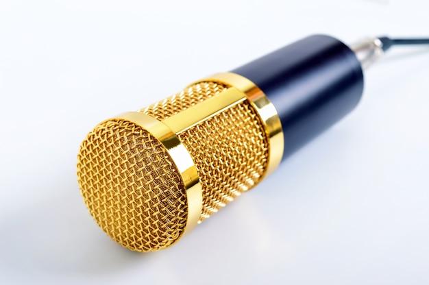 Microphone or sur surface blanche. thème musical. microphone à condensateur. fermer