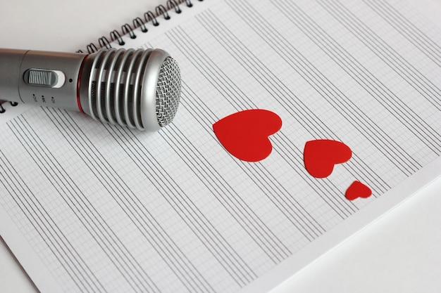 Microphone et papier coeurs rouges sur un cahier de musique propre.
