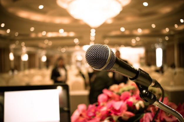 Microphone sur résumé floue de podium avant et discours dans la salle de séminaire