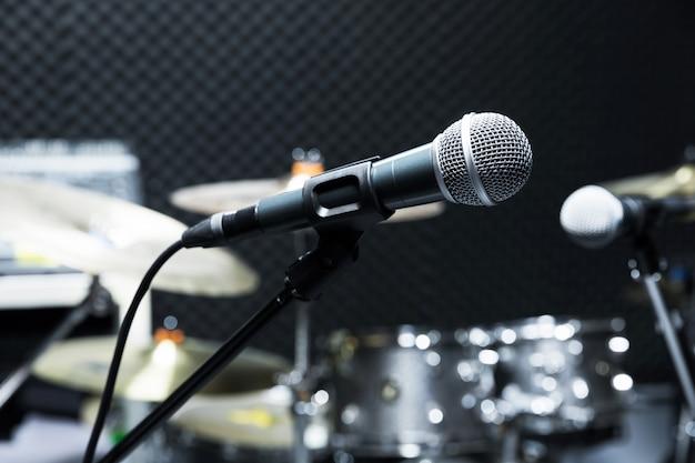 Microphone de studio à condensateur professionnel, concept musical. enregistrement, microphone de mise au point sélective dans un studio radio, microphone de mise au point sélective et guitare d'équipement musical flou,