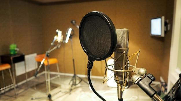 Microphone avec suspension antichoc et filtre anti-pop sur trépied et support de notes lors de l'enregistrement d'une vidéo en studio