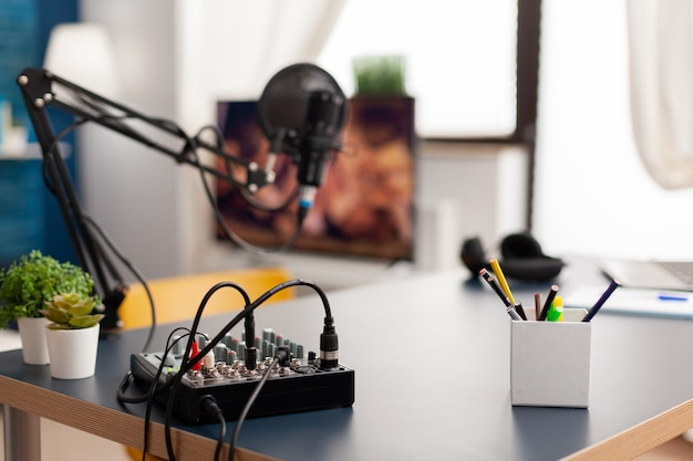 Microphone et table de mixage pour podcast du célèbre créateur. influenceur enregistrant du contenu sur les réseaux sociaux avec un microphone de production dans un home studio professionnel avec un équipement moderne