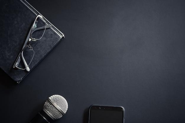 Microphone, téléphone, lunettes sur le livre avec un fond noir. opérateur de service de centre d'appels lieu de travail vide.