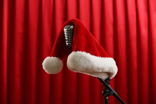 Microphone vintage avec chapeau de noël sur fond de rideau rouge