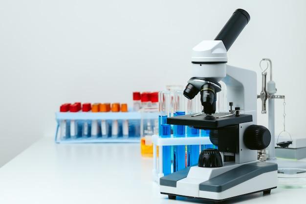 Microscope et tubes à essai sur table en laboratoire, close up
