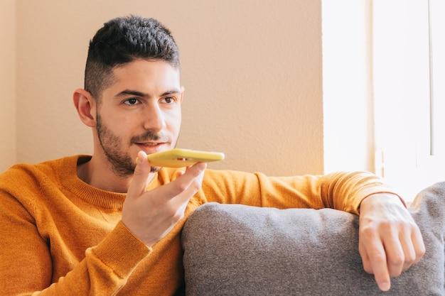 Mid adult man en vêtements jaunes sur fond gris depuis la maison, envoyant un message vocal depuis son téléphone intelligent. concept technologique et notes vocales