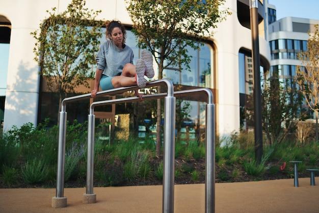 Mid adult woman faisant de l'exercice sur des barres parallèles à l'extérieur en ville, concept de mode de vie sain.