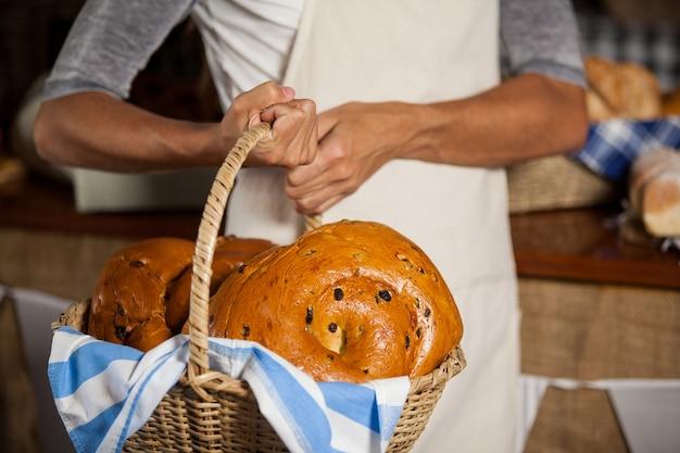 Mid-section of female staff holding panier en osier de pains au comptoir