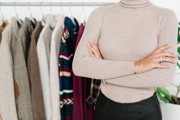 Mid-section of young woman in casualwear croisant les bras sur la poitrine en se tenant debout dans la boutique de vêtements décontractés