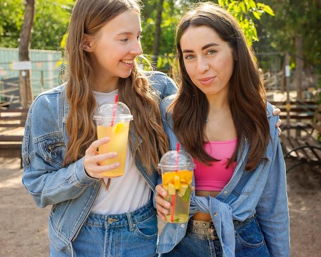 Mid shot amis tenant du jus de fruits frais