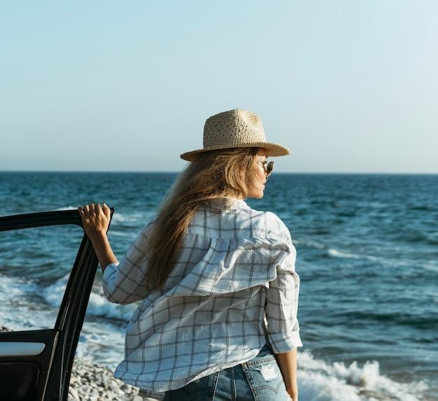 Mid shot femme blonde regardant la mer en voiture