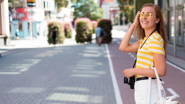 Mid shot femme avec caméra en ville