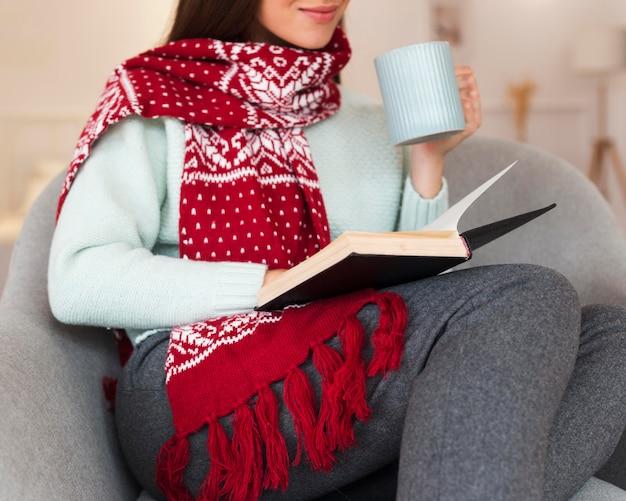 Mid shot femme confortable avec écharpe et livre