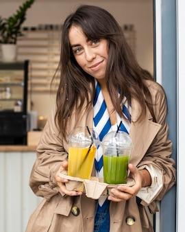 Mid shot femme avec jus de fruits frais à emporter
