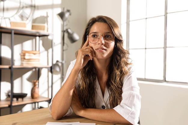 Mid shot femme avec des lunettes pensant
