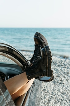 Mid shot femme pieds hors de la fenêtre de la voiture près de la mer