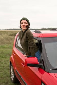 Mid shot femme sortir de la voiture de la fenêtre
