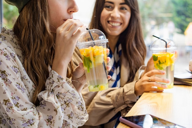 Mid shot femmes avec des boissons fraîches au café