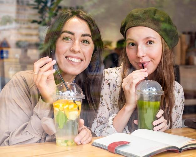 Mid shot femmes buvant des jus de fruits frais au café