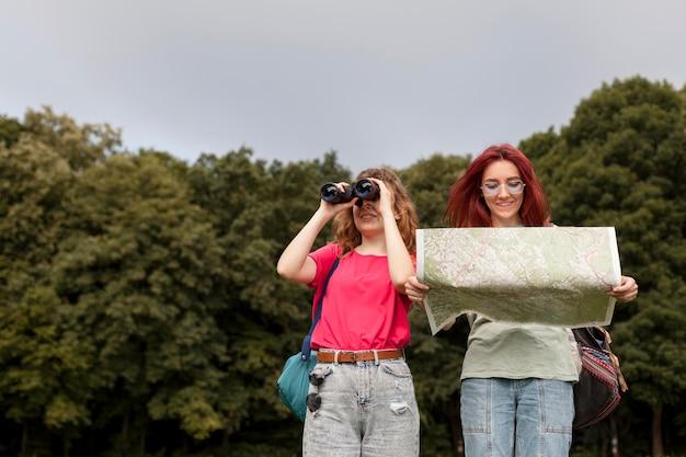 Mid shot des femmes heureuses avec des jumelles et une carte dans la nature