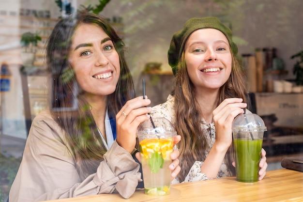 Mid shot femmes avec jus de fruits frais au café