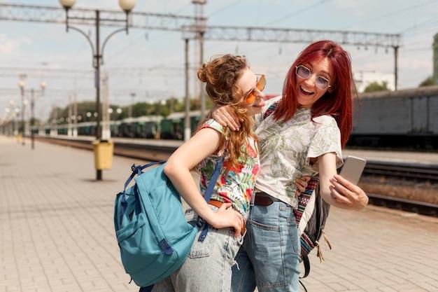 Mid shot femmes prenant selfie dans la gare