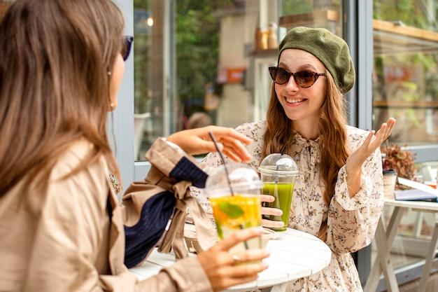 Mid shot femmes tenant des boissons fraîches et assis à table
