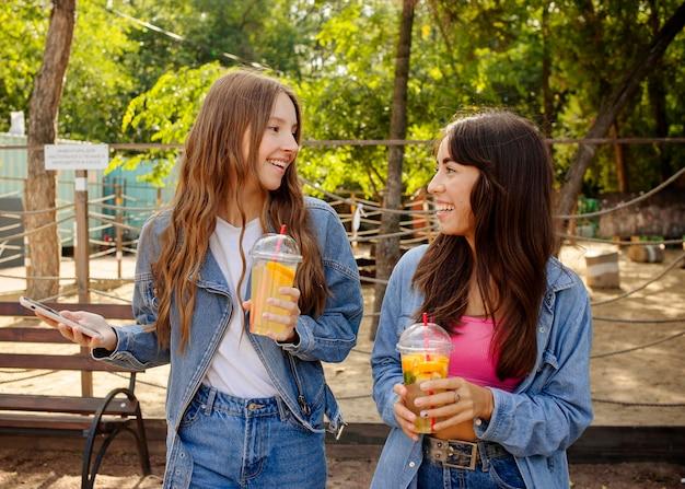 Mid shot filles tenant du jus de fruits frais