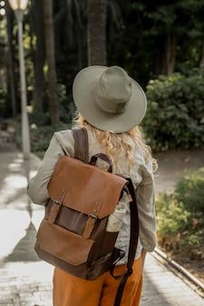 Mid shot girl avec chapeau marchant dans la nature