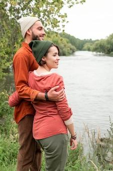 Mid shot happy couple regardant vers l'eau