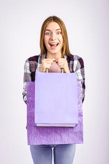 Mid shot heureux femme tenant des sacs et regardant la caméra