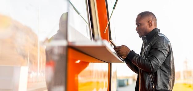 Mid shot homme noir passant commande au food truck
