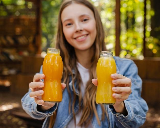 Mid shot jeune femme tenant des bouteilles de jus de fruits frais