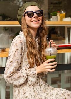 Mid shot jeune femme tenant un smoothie vert