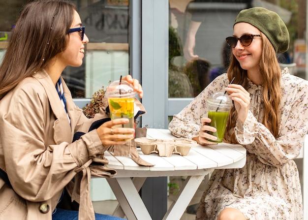 Mid shot jeunes femmes tenant des boissons fraîches et assis à table