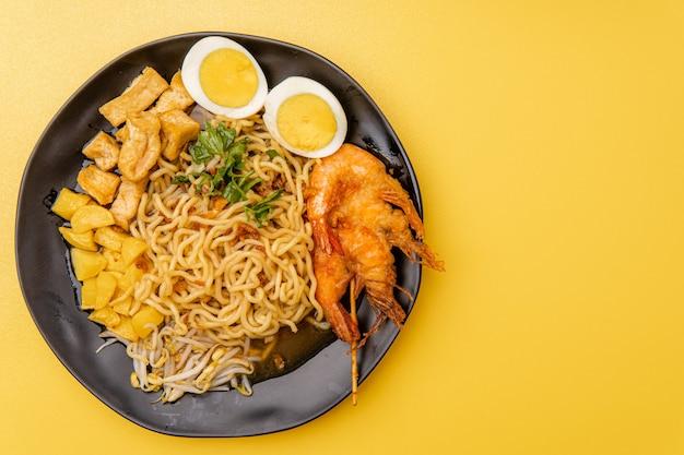 Mie rebus medan ou soupe de nouilles le plat est composé de nouilles aux œufs jaunes qui sont également utilisées à hokkien mee avec une sauce épicée légèrement sucrée au curry la sauce est à base de crevettes ou de bouillon de tauchu